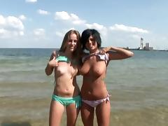Two petite beauties showing off their arousing bodies on the beach